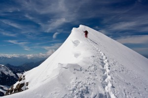 Climber descending snowy peak at high mountains