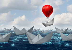 Business advantage concept and game changer symbol as an ocean with a crowd of paper boats and one boat rises above the rest with the help of a red hot air balloon as a success and innovation metaphor for new thinking.